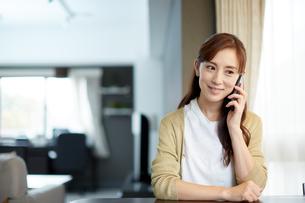 テーブルで携帯電話を使う女性の写真素材 [FYI02839861]