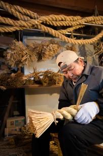 冬の農閑期にしめ縄作りする80代男性の写真素材 [FYI02839962]