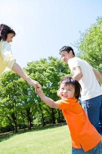 公園を手をつないで歩く3人家族の写真素材 [FYI02840083]