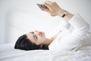 ベッドに寝転んでスマホを触っている女性の写真素材 [FYI02840086]