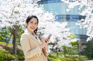 桜の前で携帯電話を使う女性の写真素材 [FYI02840109]