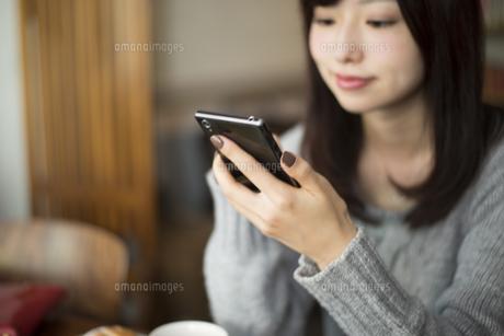 スマホを触っている女性の写真素材 [FYI02840169]