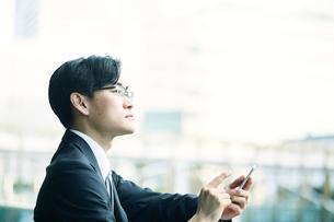 スマートフォンをもつビジネスマンの写真素材 [FYI02840171]