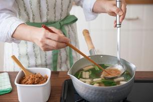 味噌を玉杓子と菜箸で鍋の中で溶かす女性の写真素材 [FYI02840385]