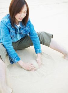 砂を集める女性の写真素材 [FYI02840777]