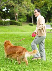 散歩する中高年の日本人男性と犬の写真素材 [FYI02841061]