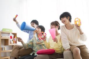 ソファーに座って応援する男女4人の写真素材 [FYI02841864]