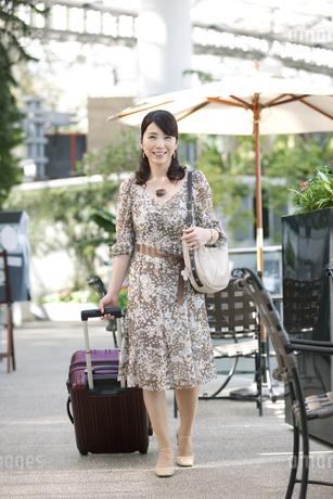 旅行かばんを持って歩く中高年女性の写真素材 [FYI02841930]