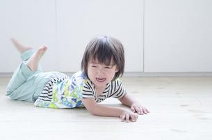 床に這いつくばって泣いている男の子の写真素材 [FYI02842355]