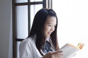 本を読んでいる制服姿の女性の写真素材 [FYI02842692]