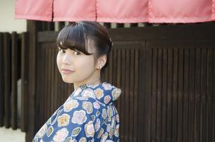 格子の家の前で振り返る着物姿の女性の写真素材 [FYI02842729]