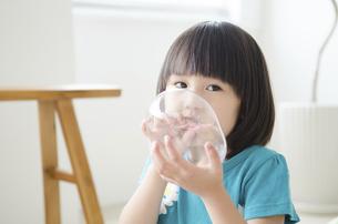 風船を膨らませている女の子の写真素材 [FYI02842750]