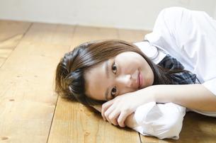 床に寝転んでこちらを見る制服姿の女性の写真素材 [FYI02842752]