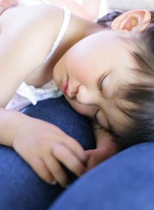 母親の膝で寝る女の子の写真素材 [FYI02843219]