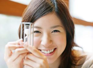 砂時計を持つ笑顔の女性の写真素材 [FYI02844154]