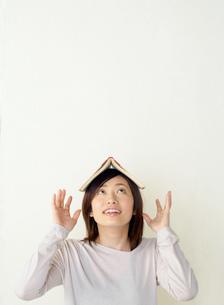 本を頭に置いて上を見る女性の写真素材 [FYI02844236]