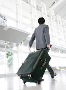 スーツケースを運ぶビジネスマンの写真素材 [FYI02844369]
