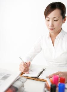 手帳を持つ女性 重ねられた新聞の写真素材 [FYI02844376]