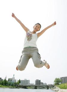 川辺でジャンプをする女性の写真素材 [FYI02844399]