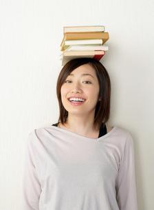 本を頭に載せた女性の写真素材 [FYI02844406]