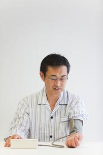血圧を測る中年男性の写真素材 [FYI02844792]
