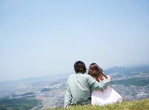 丘に座って寄り添う男女の写真素材 [FYI02844848]