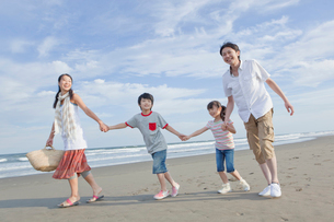 砂浜で手を繋いで歩く家族4人の写真素材 [FYI02844851]