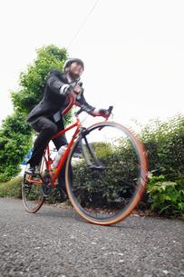 スーツ姿で自転車に乗る若い男性の写真素材 [FYI02844923]