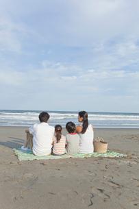 砂浜に座る家族4人の後姿の写真素材 [FYI02844976]