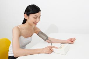 血圧を測る若い女性の写真素材 [FYI02845164]