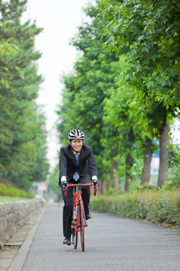 スーツ姿で自転車に乗る若い男性の写真素材 [FYI02845264]