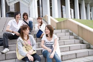 外階段に座り談笑する男女5人の写真素材 [FYI02845271]