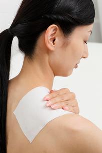 貼り薬を肩に貼った若い女性の写真素材 [FYI02845468]