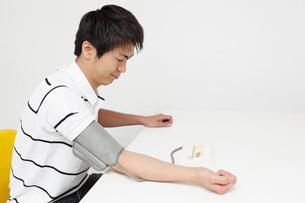 血圧を測る若い男性の写真素材 [FYI02845679]