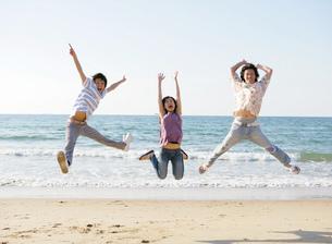 砂浜で飛び跳ねる若者たちの写真素材 [FYI02845785]