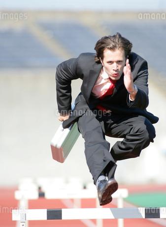 ハードルを飛び越えるビジネスマンの写真素材 [FYI02846012]