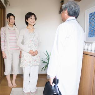 玄関で医者を出迎える患者(訪問医療)の写真素材 [FYI02846534]