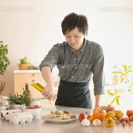 キッチンで料理をする男性の写真素材 [FYI02846557]
