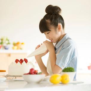 キッチンでケーキを作る女の子の写真素材 [FYI02846560]