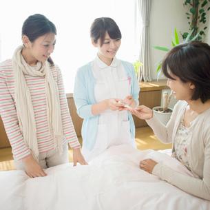 患者に体温計を渡す看護師(訪問医療)の写真素材 [FYI02846598]
