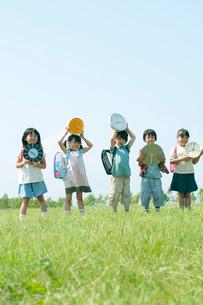 草原で時計を持つ小学生の写真素材 [FYI02846635]
