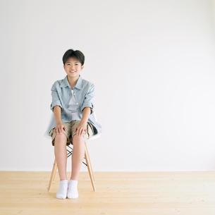 椅子に座り微笑む男の子の写真素材 [FYI02846659]