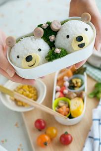 クマのキャラクター弁当を持つ女性の手元の写真素材 [FYI02846661]