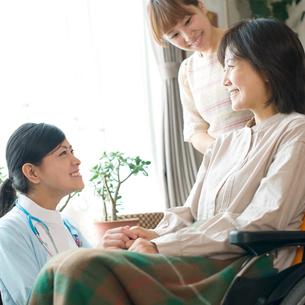 患者の手を握る看護師(訪問医療)の写真素材 [FYI02846837]