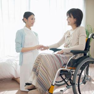 車椅子に乗る患者の手を握る看護師(訪問医療)の写真素材 [FYI02846921]