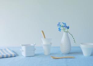ブルーの布に飾った白い食器と青い花の写真素材 [FYI02847020]