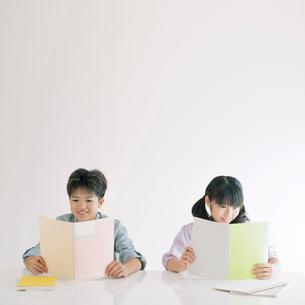 ノートを持ち微笑む男の子と女の子の写真素材 [FYI02847082]