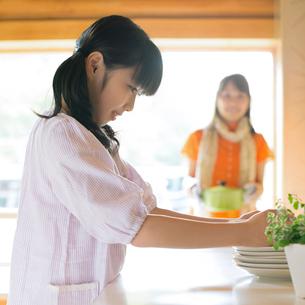 キッチンで手伝いをする女の子の写真素材 [FYI02847122]