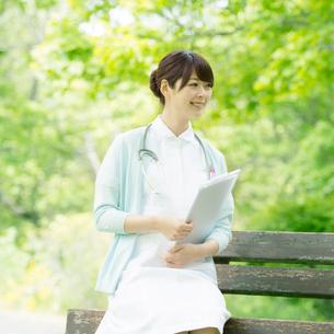 ベンチに座り微笑む看護師の写真素材 [FYI02847165]