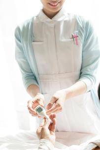患者に体温計を渡す看護師(訪問医療)の写真素材 [FYI02847195]